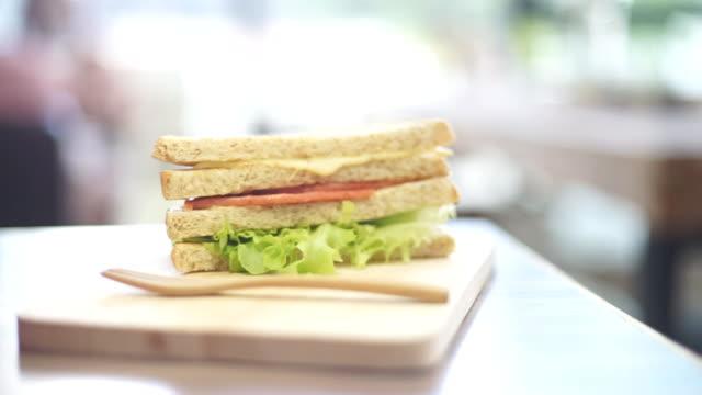 Bologna und Käse Vollkorn-Sandwich auf Holzbrett.