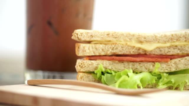 vídeos de stock e filmes b-roll de bologna and cheese whole wheat sandwich on wooden board. - sanduíche