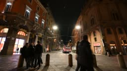Bologna, Italy - Unknown people stroll followed by the shadows of the night