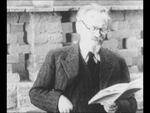 Bolshevik revolutionary Leon Trotsky reads aloud from pamphlet / WS Russian cadets march in 1910s / procession of marchers winds through street...