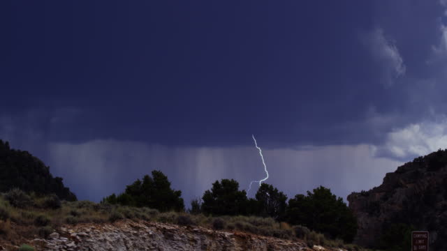a bolt of lightning flashes during a rainstorm in flaming gorge, utah - montagne rocciose video stock e b–roll