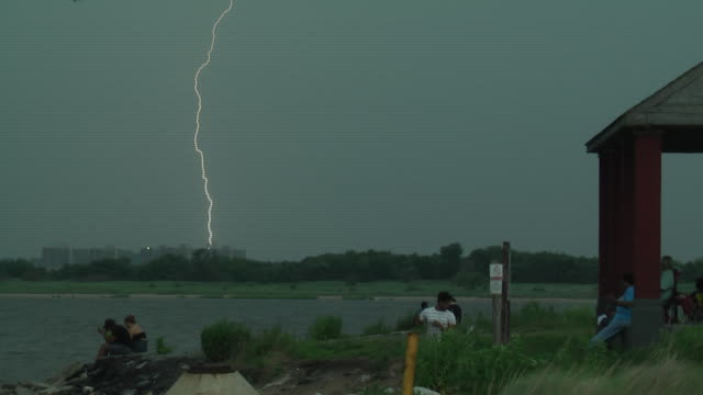 a bolt of lightning strikes in the distance as a thunderstorm threatens beach goers along the shoreline of jamaica bay in howard beach queens new... - scott mcpartland stock videos & royalty-free footage