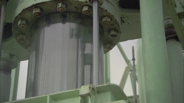 bolts hold a cylinder in place on a large machine. - bolt stock videos & royalty-free footage