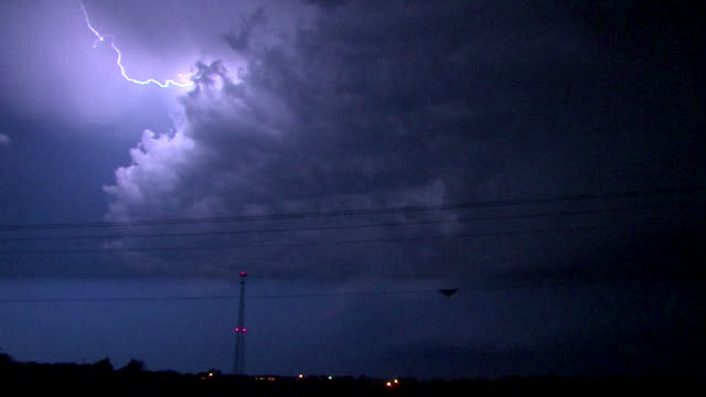 Bolts of lightning shoot out of a supercell thunderstorm at night during the height of tornado season in Oklahoma