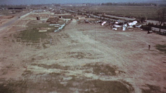 bomb craters and damaged equipment in wrecked airfield / germany - air raid stock-videos und b-roll-filmmaterial