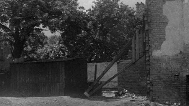 1945 b/w pan bomb damaged slum housing with children playing in yard / coventry, west midlands, england - 1945 stock videos and b-roll footage