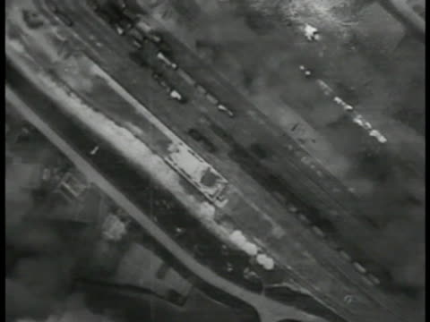 bomb shells dropping over land. b-17 flying fortress airplane dropping shells. xha bombs exploding hitting targets land. three b-17's in flight.... - bombenanschlag stock-videos und b-roll-filmmaterial