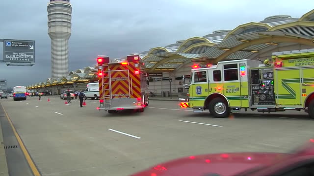 bomb squad truck with flashing sirens drives up to reagan national airport to respond to report of suspicious package. pan left to follow truck as it... - ロナルド レーガン ワシントン国際空港点の映像素材/bロール