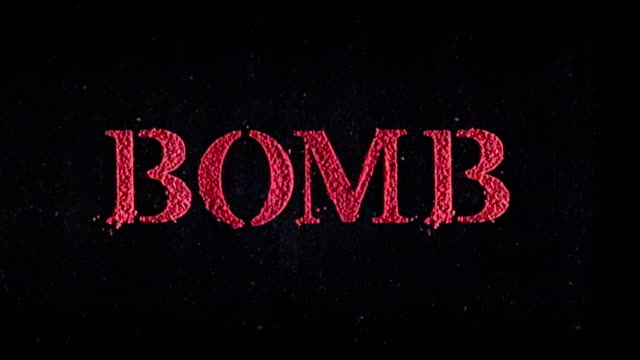 Bomb written in red powder exploding in slow motion.