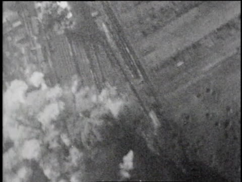 MONTAGE bombardier checking target through rangefinder / AERIAL bombs falling and exploding on impact / WS soldiers running / WS enemy soldiers...