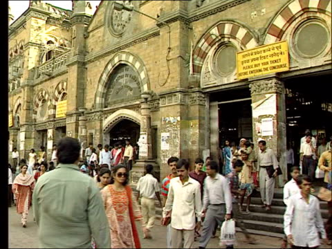 bombay commuters about by bombay station gvs busy street as people to and fro men carrying wicket baskets of vegetables on heads at market - wicket stock videos and b-roll footage
