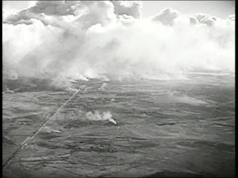 bombed, burning, smoking land. smoking land cockpit w/ pilots. aerial industrial area smoking, two round stacks w/ smoke, no tops. european town or... - poland stock videos & royalty-free footage