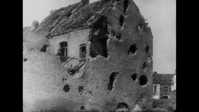 vidéos et rushes de bombed out building w crosses marking soldiers' graves in foreground / pan across to building damaged by shell fire / ruins of building with people... - première guerre mondiale