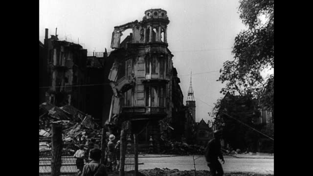 bombed out buildings in postwar cologne are brought down / fire engine pulling down the front of buildings as resident watch / former nazis forced to... - 1945 stock-videos und b-roll-filmmaterial