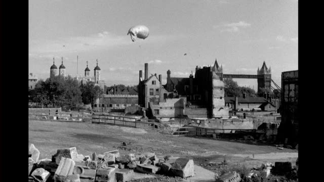 bombed out london neighborhood virtually all buildings destroyed or damaged / tower of london and tower bridge seen in background / barrage balloon... - tower bridge stock videos & royalty-free footage