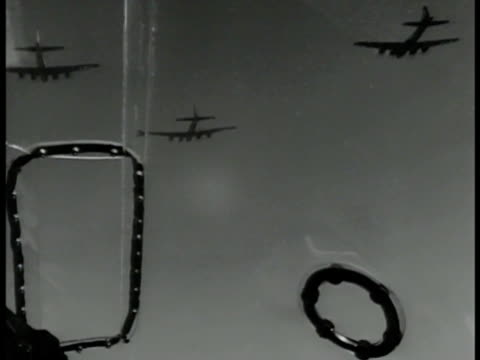 bomber airplanes flying. int pilots in cockpit. overhead: bombs dropping . nose of b-17 flying fortress bomber airplane. overhead: city in smoke.... - 爆撃機点の映像素材/bロール