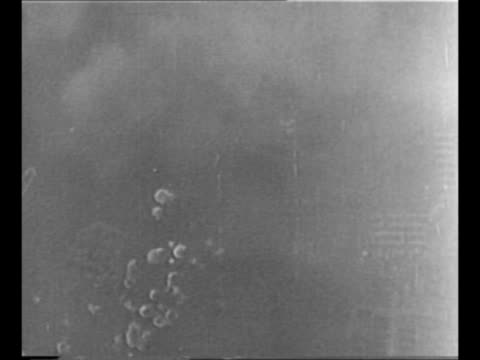 bomber drops firebombs as it flies over japan during world war ii / from bomb bay as bombs drop / aerial explosions on ground / side view from camera... - 空爆点の映像素材/bロール