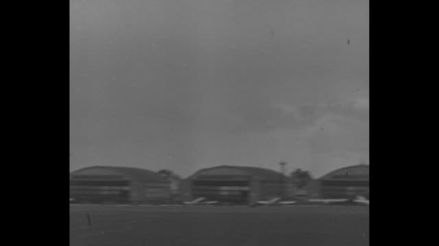 vídeos de stock, filmes e b-roll de bomber flying low over airfield / crowd at airfield watching air show / fighter plane flying low over airfield / vs bombers flying low over airfield - 1936