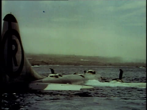 b29 bomber in water under thick clouds crew climbing out onto the fuselage / iwo jima japan - schlacht um iwojima stock-videos und b-roll-filmmaterial
