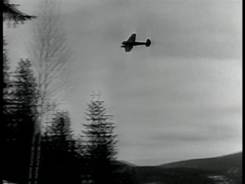 stockvideo's en b-roll-footage met bomber plane flying over smoking town. town w/ houses burning w/ smoke people on street. nazi bomber plane descending to land. man on ship looking... - tweede wereldoorlog