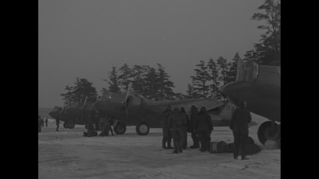 bomber taxiing towards row of parked bombers / pan across row of parked bombers / two shots of men standing around parked bomber / man pulling on... - army helmet stock videos & royalty-free footage