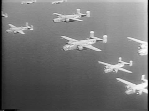 stockvideo's en b-roll-footage met bombers drop bomb over shoreline in japan / montage of b25 bombers flying in formation in sky - stille zuidzee