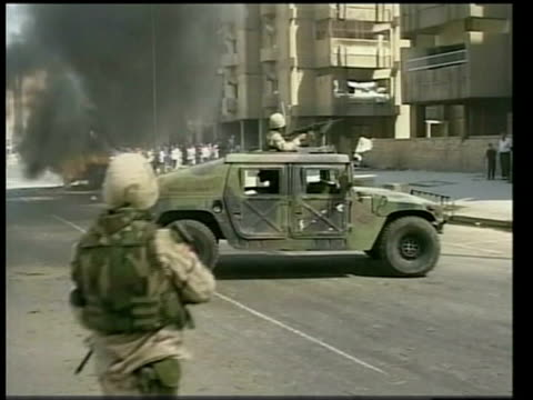 reaction; lib mat held washington bureau iraq: baghdad: ext gv us jeep on fire in street soldier on patrol next to armoured vehicle as jeep burns in... - イラク点の映像素材/bロール