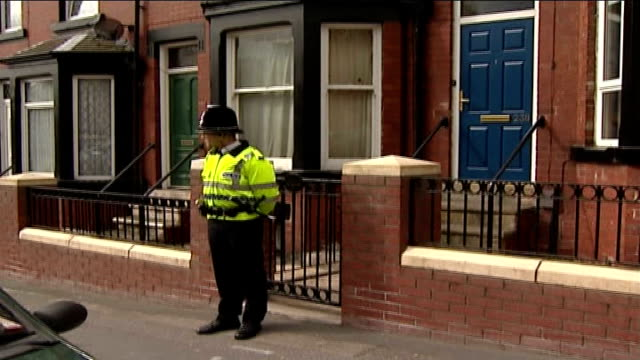 arrested including widow of ringleader; leeds: beeston: police officer standing guard outside house - witwe stock-videos und b-roll-filmmaterial