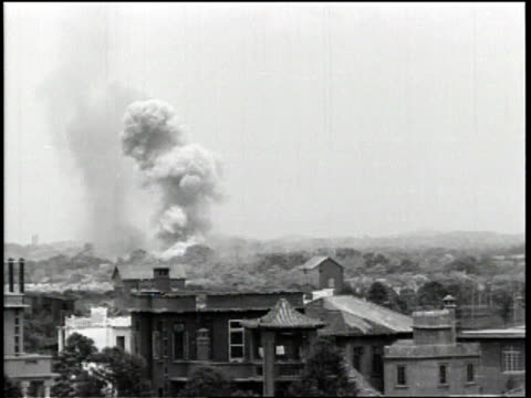 bombs and smoke on the changsha china skyline after a japanese air attack / a man nervously smokes a cigarette / - 煙草製品点の映像素材/bロール