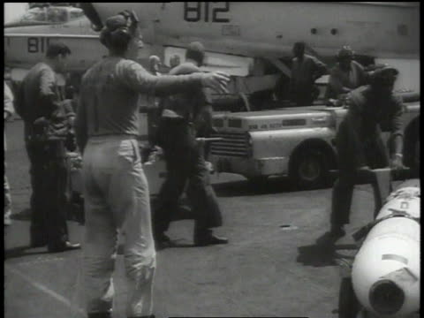Bombs being loaded onto wings of planes /