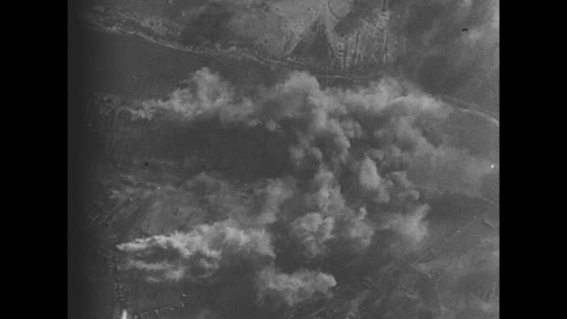 Bombs dropping falling high over the ground with the resulting explosions and smoke/ Note exact day not known