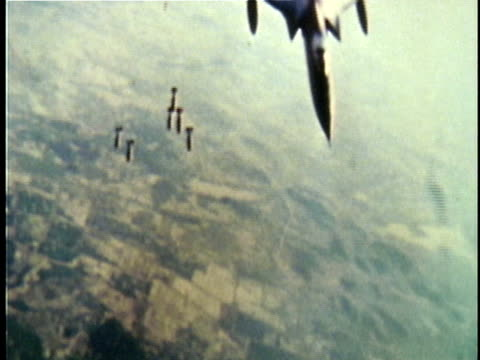 vidéos et rushes de bombs dropping from us fighter plane over countryside during vietnam war / north vietnam - 1964