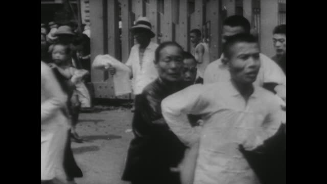 stockvideo's en b-roll-footage met wwii bombs drops from japanese planes as civilians run for cover during the battle of shanghai - 1937