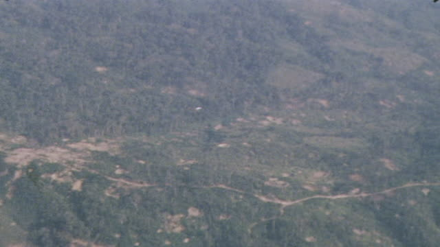 Bombs tumbling through the air over dense jungle and rocky ravine / Vietnam