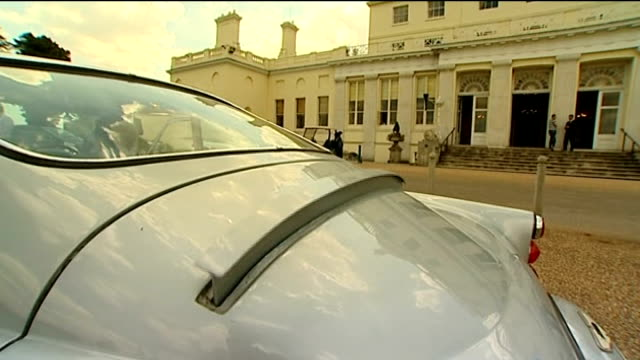 Bond car to be auctioned Reporter to camera as lifts lid on gadgets inside car Bullet deflector shield being raised at back of car and numberplate...