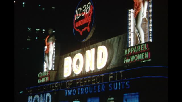 vidéos et rushes de 1954 montage bond store illuminated at night, times square, new york city, new york, usa - 1954