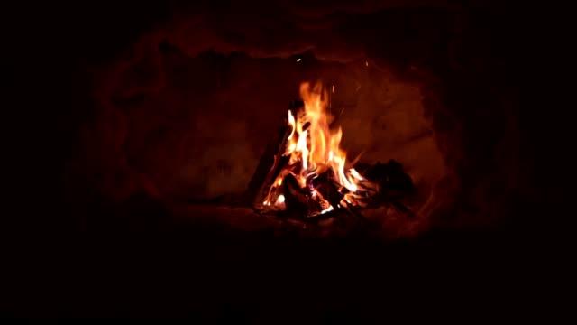 雪を頂いた山の失われた観光客のグループのための熱を提供するイグルーの中の焚き火 - brightly lit点の映像素材/bロール