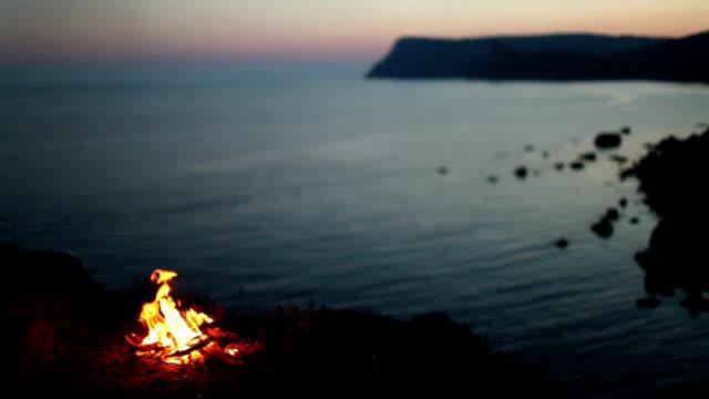 vídeos de stock e filmes b-roll de fogueira perto do mar - fogueira de acampamento