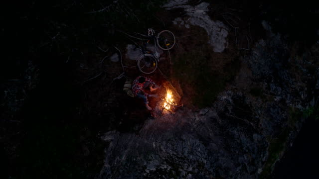 bonfire on a lake shore. man warming up by the fire. drone point of view - firewood stock videos and b-roll footage