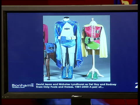 bonhams auction of film costumes; auctioneer taking bids buyers / screen displaying pair of batman and robin suits pull out models running up to... - nicholas lyndhurst stock videos & royalty-free footage