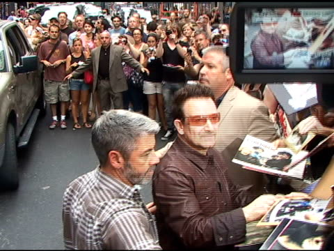 Bono signs autographs for fans as he arrives at the 'Late Show With David Letterman' in New York 07/18/11