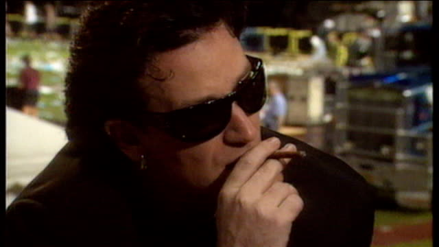 Bono speaking with reporter Tsehai Tiffen about 1993 Zooropa concert tour while smoking cigar and possibility of calling host Paul Holmes during...