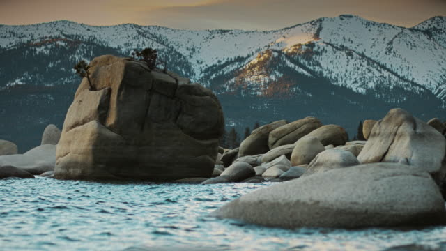 bonsai rock surrounded by mountains at lake tahoe - boulder rock stock-videos und b-roll-filmmaterial