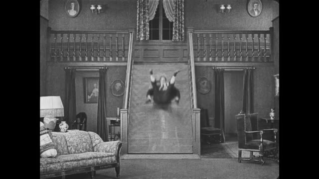 vidéos et rushes de 1921 booby-trapped steps disappear from beneath unsuspecting man (buster keaton) and he slides to bottom of staircase - steps and staircases