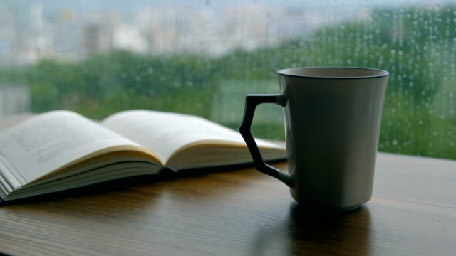 book and coffee cup on wooden table in rainy day - reminder stock videos & royalty-free footage