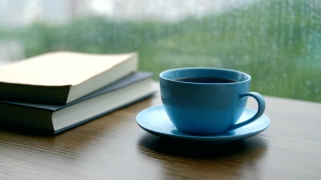 buch und kaffeetasse auf holztisch an regnertag - gedächtnisstütze stock-videos und b-roll-filmmaterial