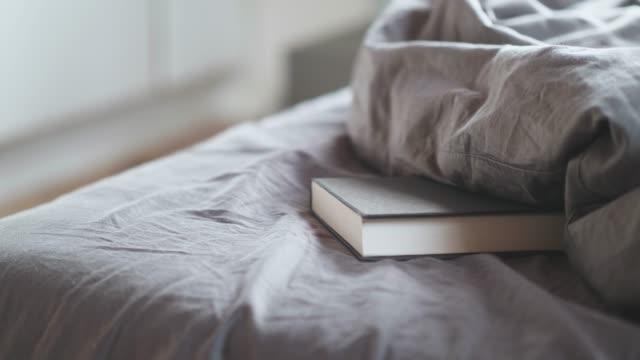 vídeos de stock, filmes e b-roll de um livro na cama em casa - cômodo de casa