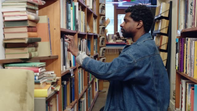 book lover scanning shelves in used bookstore - book shop stock videos & royalty-free footage