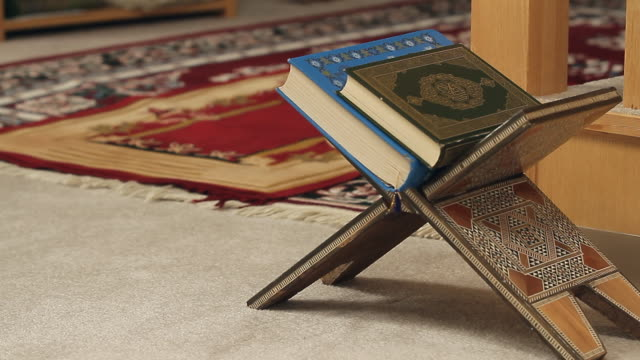 a book of the koran on a book holder - koran stock videos and b-roll footage