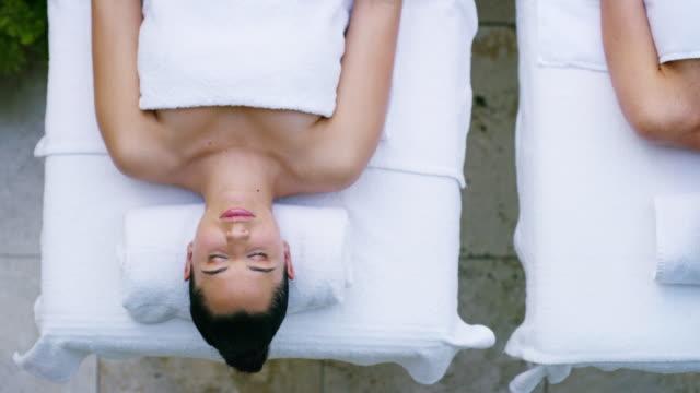 boka dig en spa-dag med din favorit person - massage table bildbanksvideor och videomaterial från bakom kulisserna